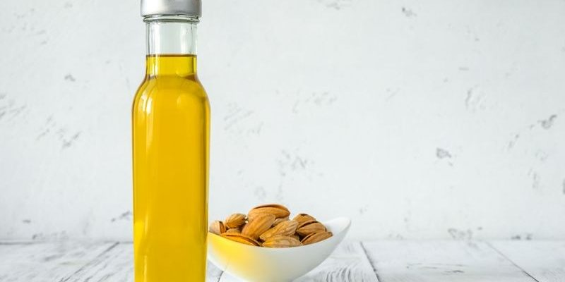 Bottle of almond oil with almonds