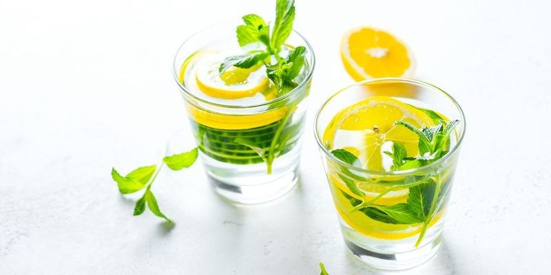 Infused water in glasses on white background. Healthy food drink concept. Closeup with copy space.