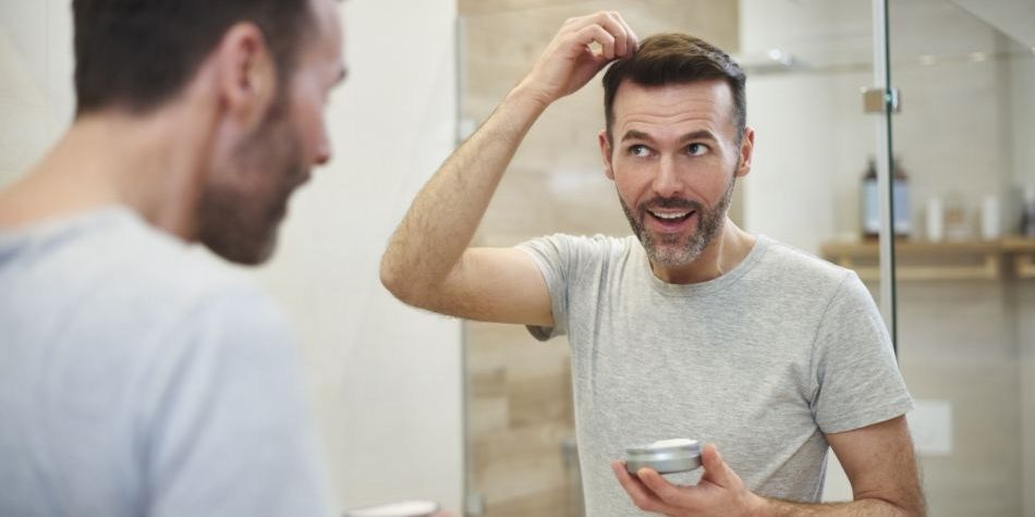 Mature man applying hair gel in the bathroom