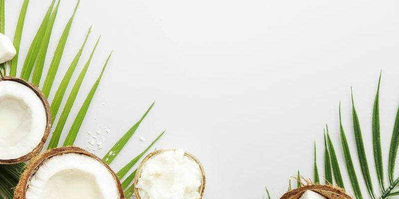 Coconuts products - mct butter, oil, milk, oil, shavings on grey background. Copy space. Hair, skin and body treatment concept